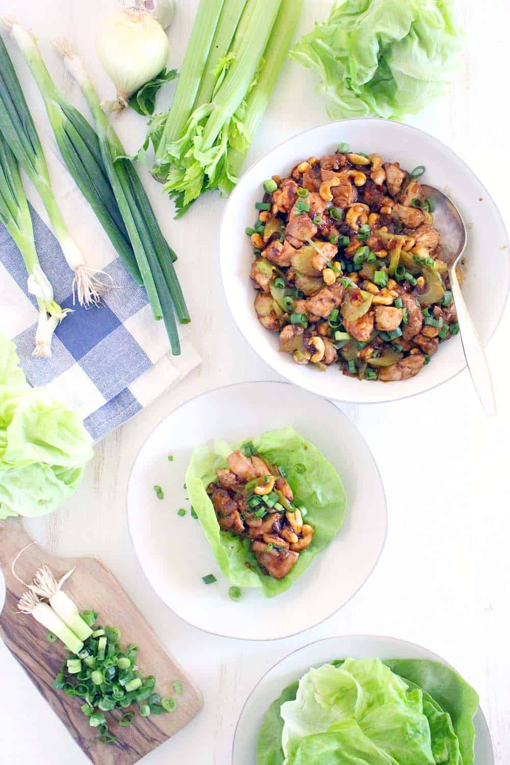 Bird's eye view of a bowl of chicken and cashew mixture next to a plate with an open leaf of lettuce with some of the mixture in the middle.