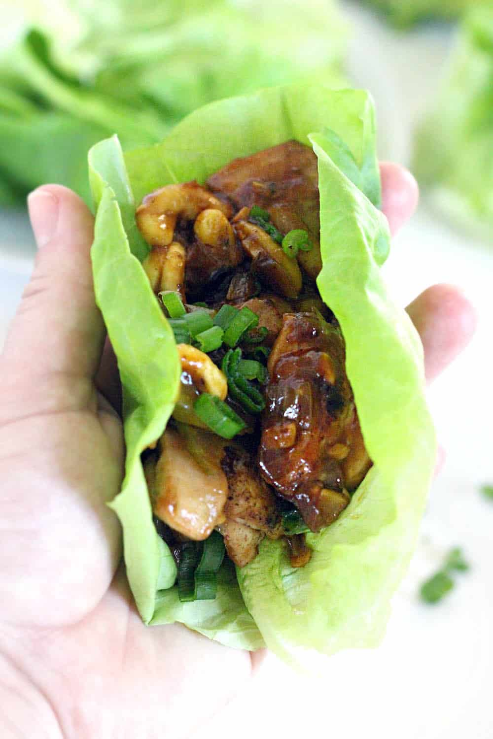 Close up of a chicken and cashew lettuce wrap, being held by a light-skinned hand.
