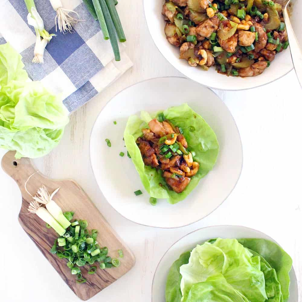 Bird's eye view of chicken and cashew lettuce wrap o a white plate, with a cutting board, veggies, a folded blue and white cloth, and a bowl of chicken and cashew mixture surrounding it.