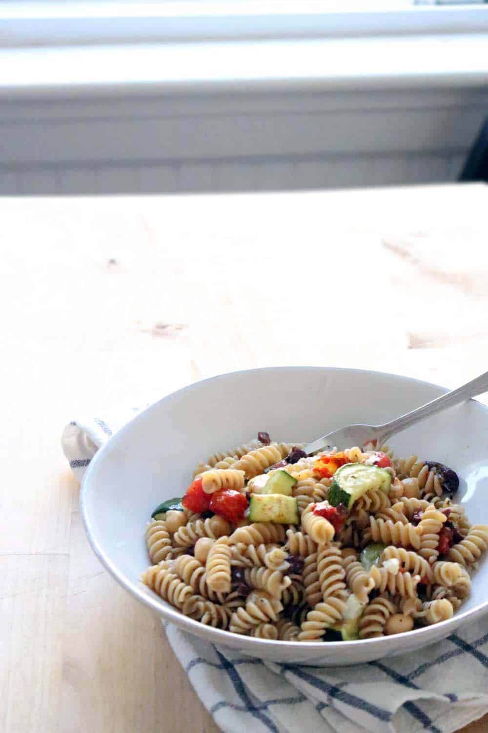 Antipasto Pesto Salad | This pasta salad is DELICIOUS, easy to make in bulk, and is served cold so it can be made ahead of time and pulled right out of your fridge before serving. The dressing makes for a salty-sweet flavor combination that's awesome for a hot summer's day. Plus, it's 100% real, clean, and unprocessed!
