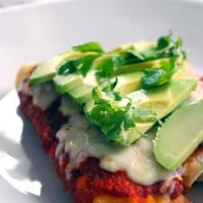 Close up of enchiladas on a white plate, garnished with avocado and herbs.