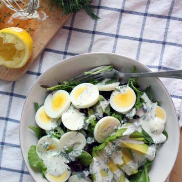 Bird's eye view of mixed greens salad topped with egg and avocado in a white bowl, on a blue checkered cloth.