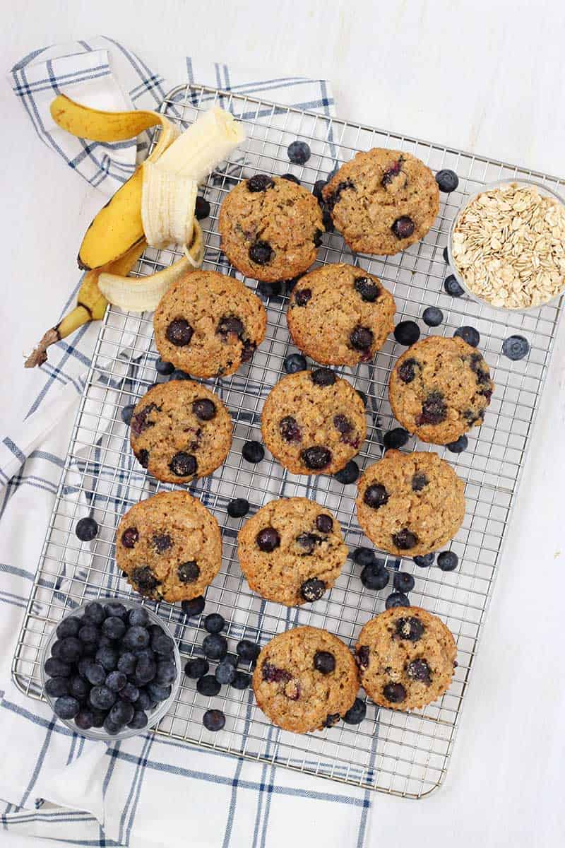 Bird's eye view of muffins on a cooling rack, with blueberries, a banana, and oats scattered around.