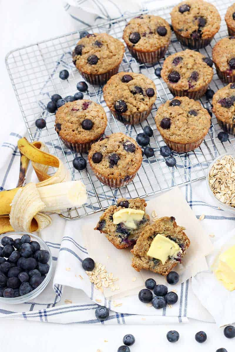 Display of muffins, blueberries in a bowl, an opened banana, and oats, all on a wooden cutting board and cooling rack.