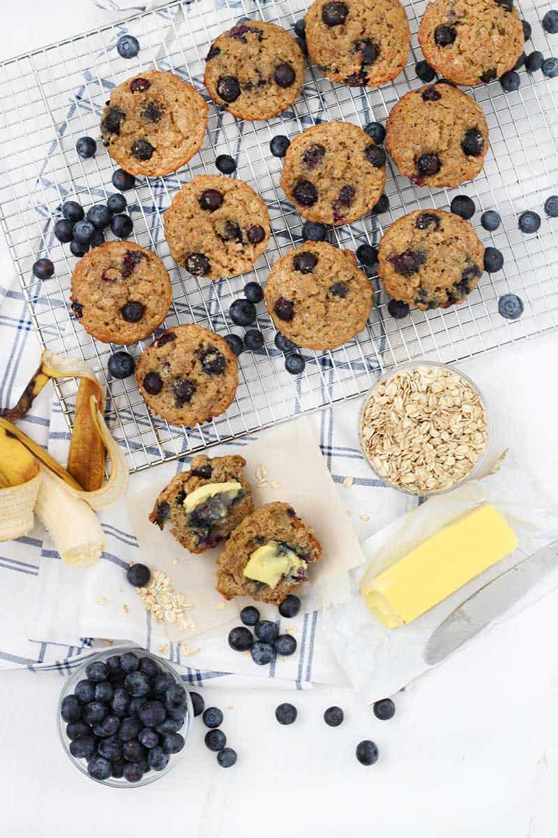Bird's eye view of muffins on a cooling rack, one muffin cut in half with a pat of butter, a banana, a bowl of oats, a bowl of blueberries, and a stick of butter.