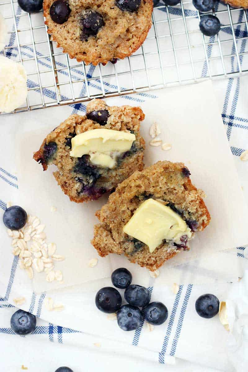 Muffin cut in half with a pat of butter, on a wooden cutting board with blueberries scattered around.