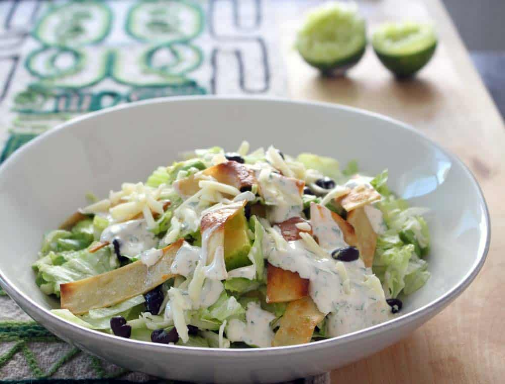 Taco salad in a white bowl on a geometric patterned cloth, with two squeezed lime halves in the background.