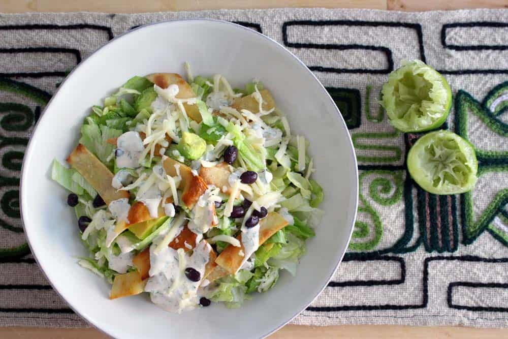 Bird's eye view of salad in a white bowl on a geometric patterened cloth, with two squeezed limes on the side.