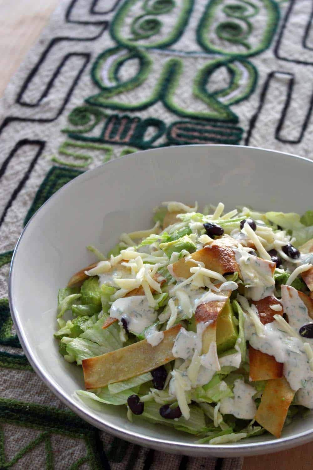 Taco salad in foreground, on geometric patterned cloth, with squeezed limes in background.