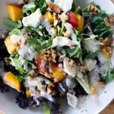 Bird's eye view of mixed greens salad with peaches, goat cheese, and walnuts in a white bowl.