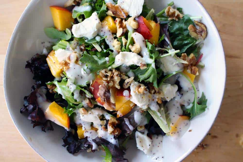 Mixed Greens Salad with Peaches Goat Cheese and Walnuts | Fresh sweet summer peaches pair very well with tart goat cheese. Add crunchy walnuts and some greens to the mix with poppy seed dressing and you have a delicious, healthy summer salad!