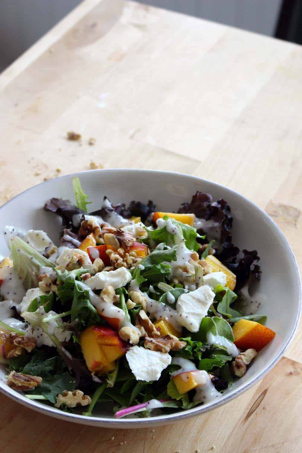 Mixed greens salad with peaches, goat cheese, and walnuts in a white bowl and set on a on a wooden cutting board.
