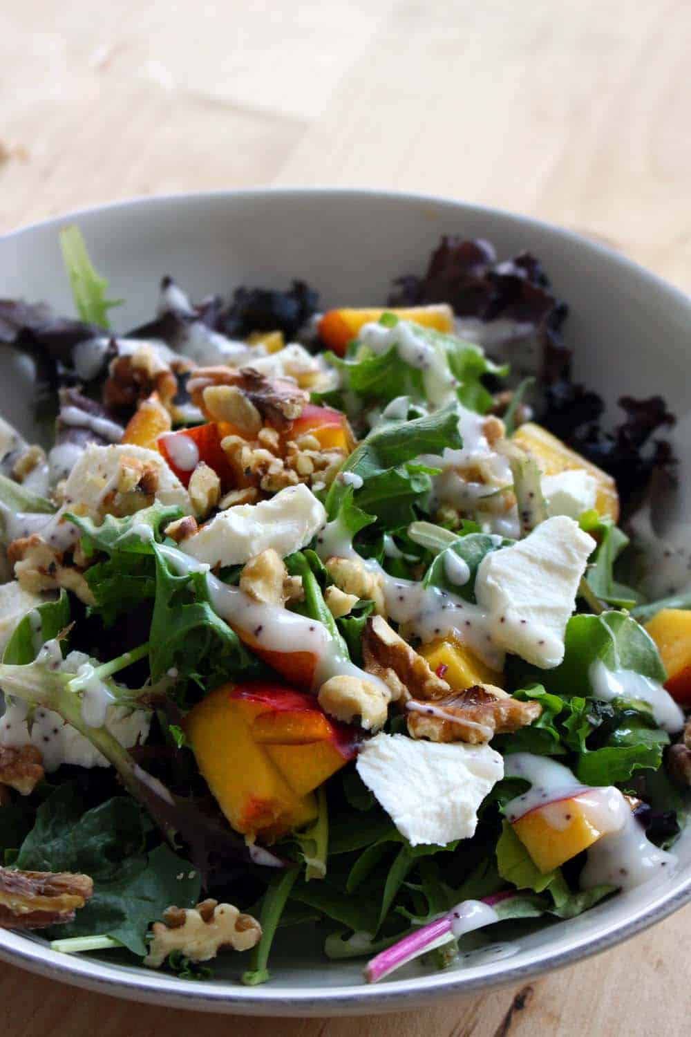 Close up of mixed greens salad with peaches, goat cheese, and walnuts in a white bowl.