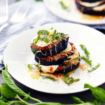 Roasted eggplant parmesan stack on a white plate with fresh basil chiffonade on top