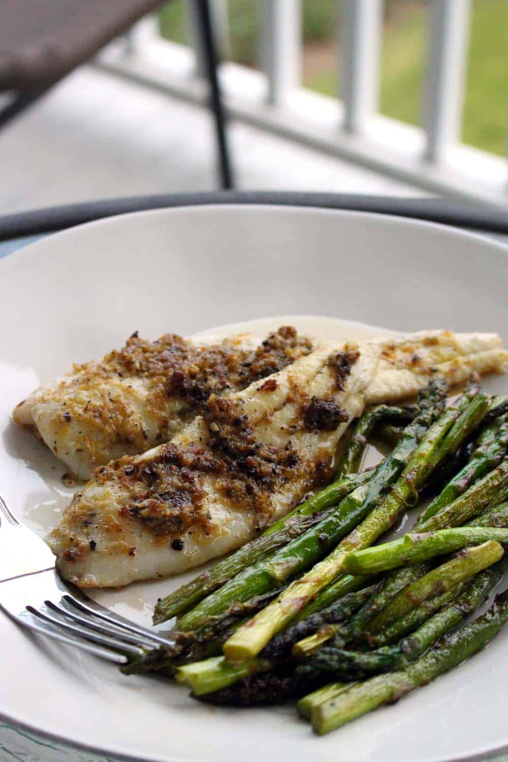 White plate holding browned white fish next to asparagus, on a table on a porch.