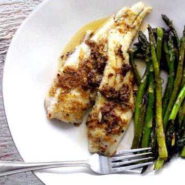 Bird's eye view of browned white fish with asparagus on a white plate, with a fork perched on the plate's edge.