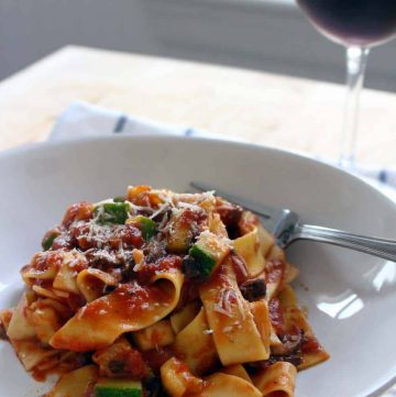 White plate holding pappardelle pasta coated with red sauce, being twirled with a fork. A glass of red wine is in the background.