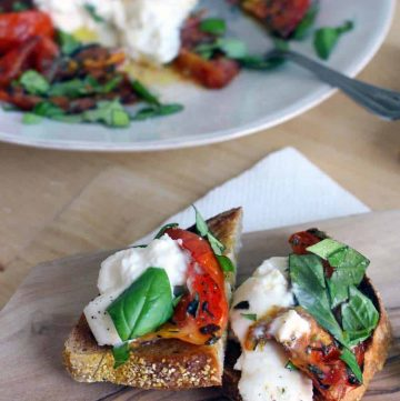 Halved roasted tomato and burrata toast on a wooden cutting board, with a white plate holding recipe ingredients in the background.
