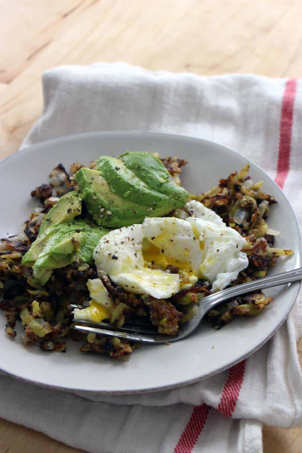 White plate holding veggie burger hash browns, sliced avocado, a poached egg, and a fork.