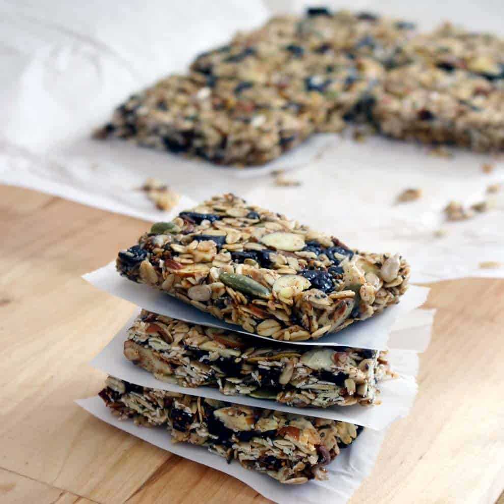 Three granola bars stacked on top of each other with parchment paper in between, and a sheet of cut up granola bars on parchment paper in the background.