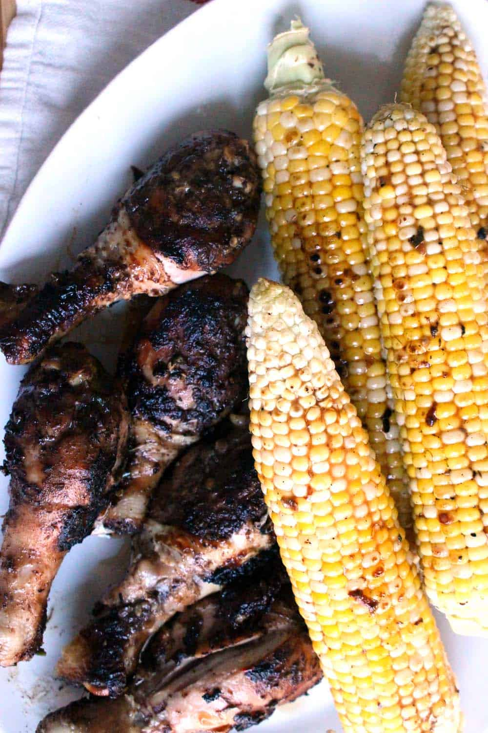 Bird's eye view of four grilled ears of corn on the cob next to several grilled and seasoned chicken drumsticks.