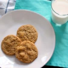 Bird's eye view of three cookies on a white plate, on a turquoise cloth with a glass of milk on the side.