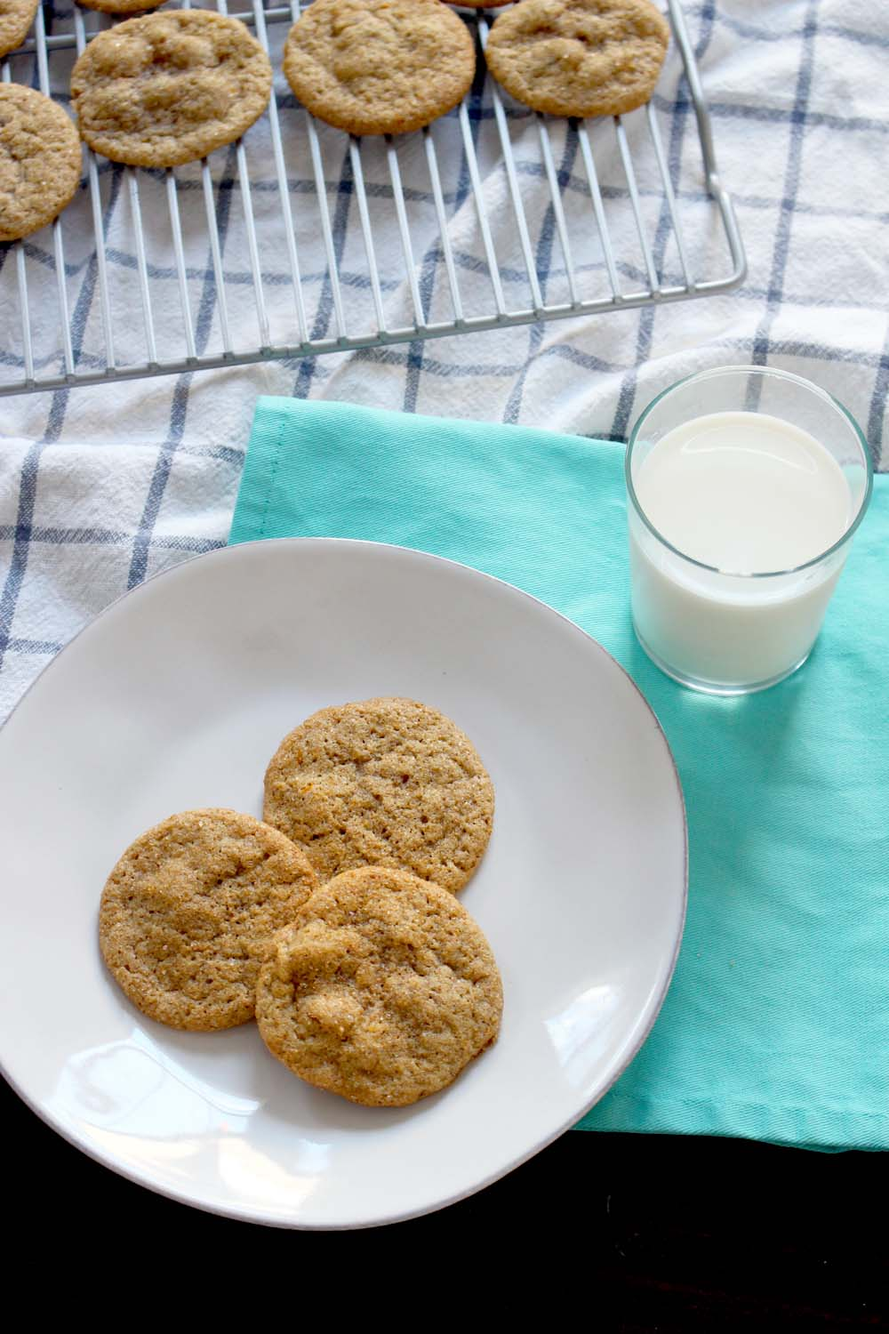 Bird's eye view of three cookies on a white plate, on a turquoise cloth with a glass of milk on the side, and a wire cooling rack holding several cookies in the background.