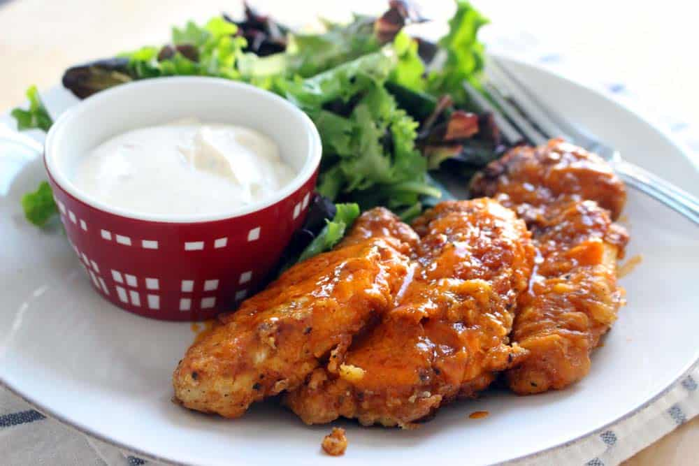 White plate holding buffalo chicken fingers, mixed greens, and a ramekin full of creamy white dipping sauce.