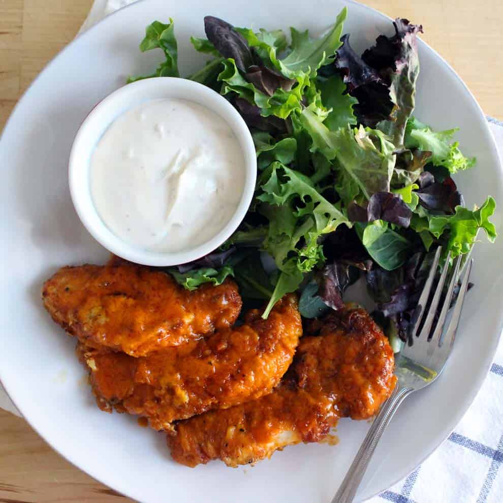 Bird's eye view of white plate holding buffalo chicken fingers, mixed greens, and a ramekin full of creamy white dipping sauce.