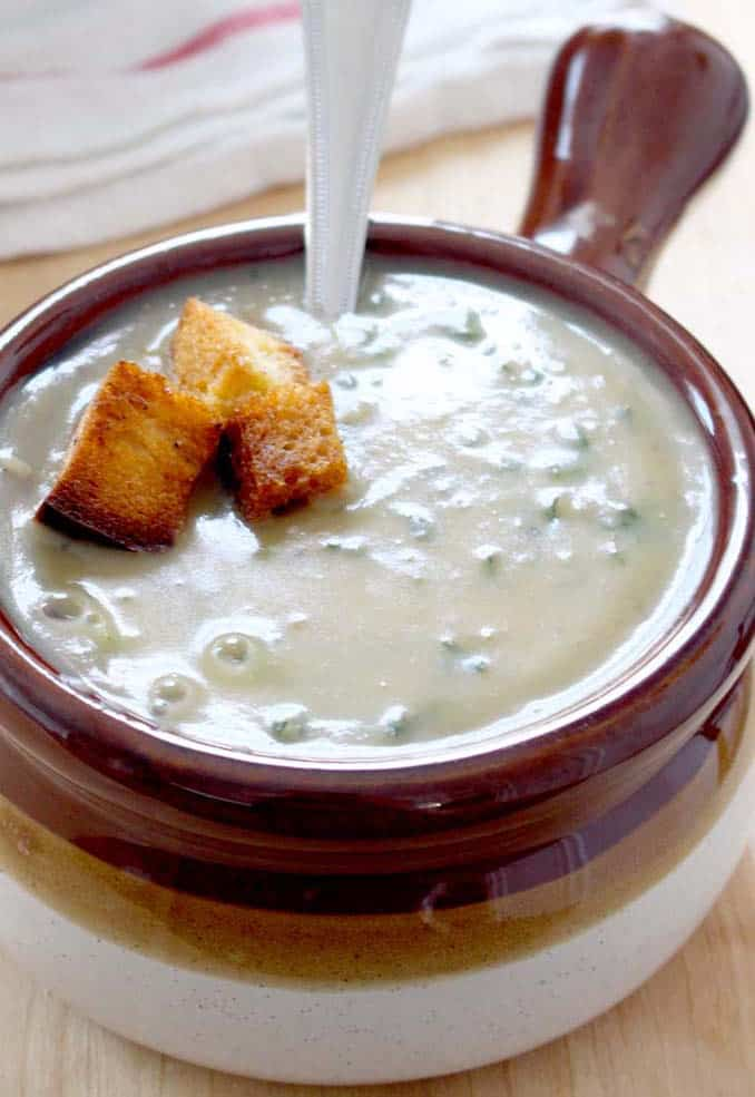 Close up of a brown ceramic bowl with handle, filled with creamy soup and garnished with croutons, with a silver spoon perched inside.