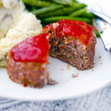 Square photo of a mini meatloaf sliced in half with green beans and potatoes.