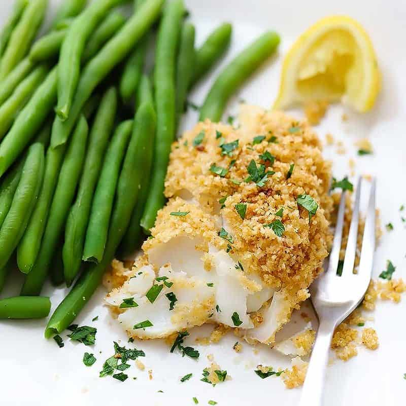 New England Baked Haddock on a plate with green beans, a lemon, and a fork