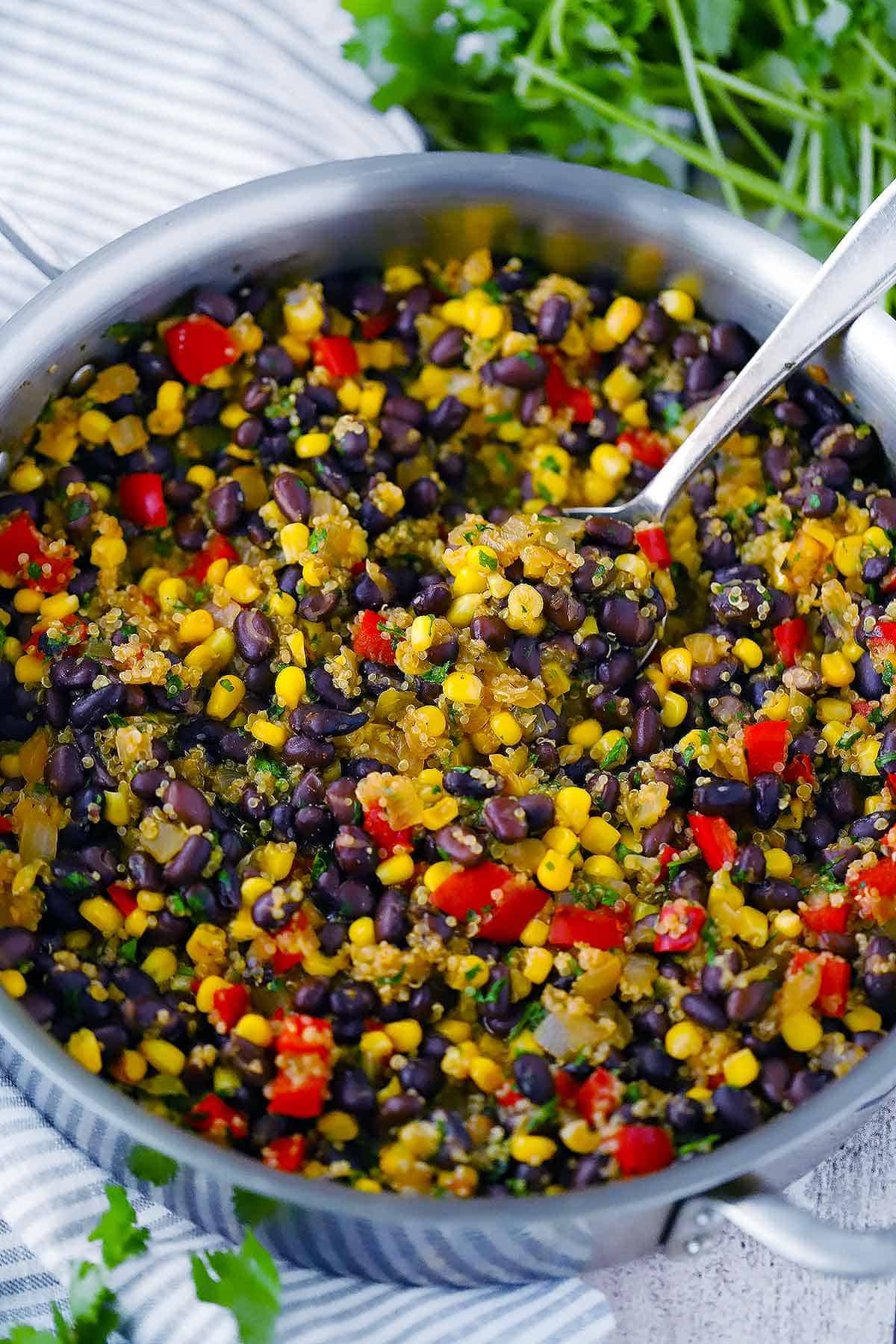 A large deep skillet with black beans and quinoa and a spoon scooping it out.
