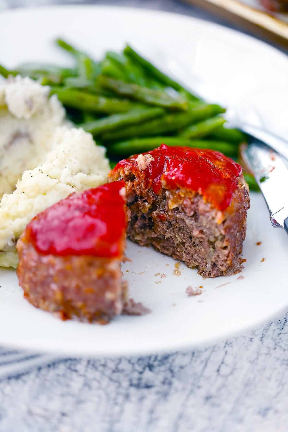 White plate holding meatloaf, mashed potatoes, and green beans.