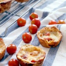 Two mini tomato pies in the foreground on a blue and white striped cloth with tomatoes scattered around them. A wooling rack holding more tomato pies is in the background.