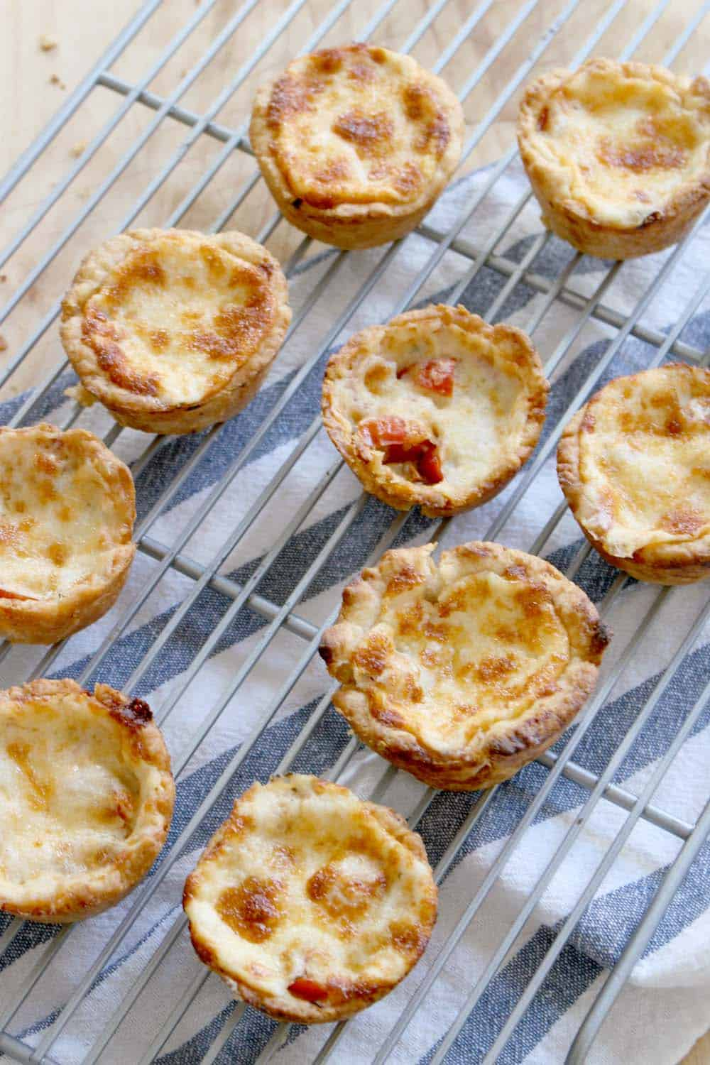 These mini tomato pies are rich and decadent, warm, and the ultimate comfort food. Perfect for lunch or dinner with a side salad, as a snack, or as an appetizer for a party! Can be individually frozen for a super convenient treat.