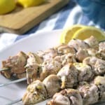 White plate holding four skewers of chicken, with lemon wedges on the side.