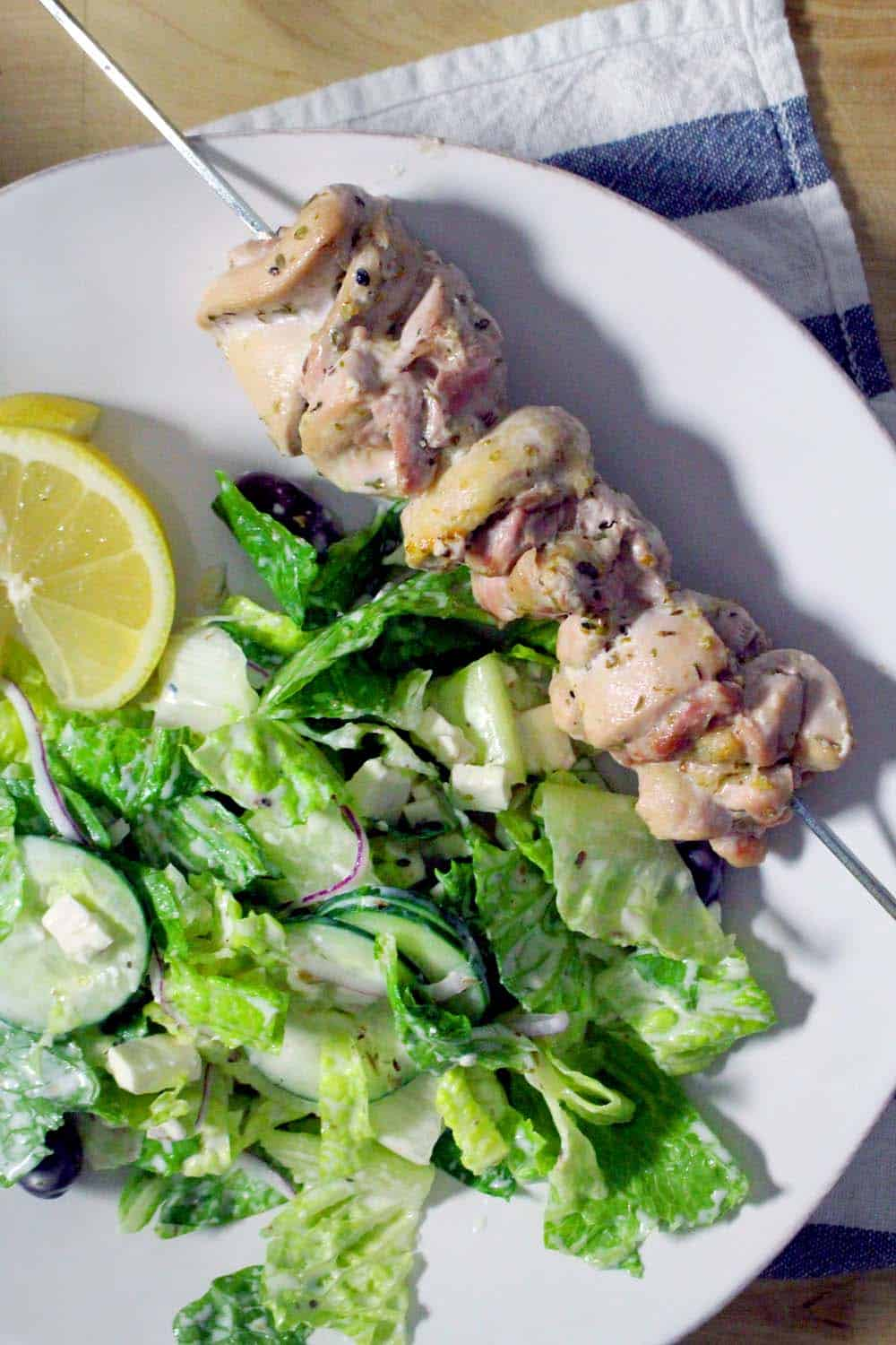 Lemon Chicken Souvlaki and Salad | This meal is healthy, hearty, easy to make, and bursting with Greek flavor. The chicken is marinated in a delicious, yogurt-based dressing and then baked to juicy perfection on skewers. The extra dressing is used on a traditional Greek salad.