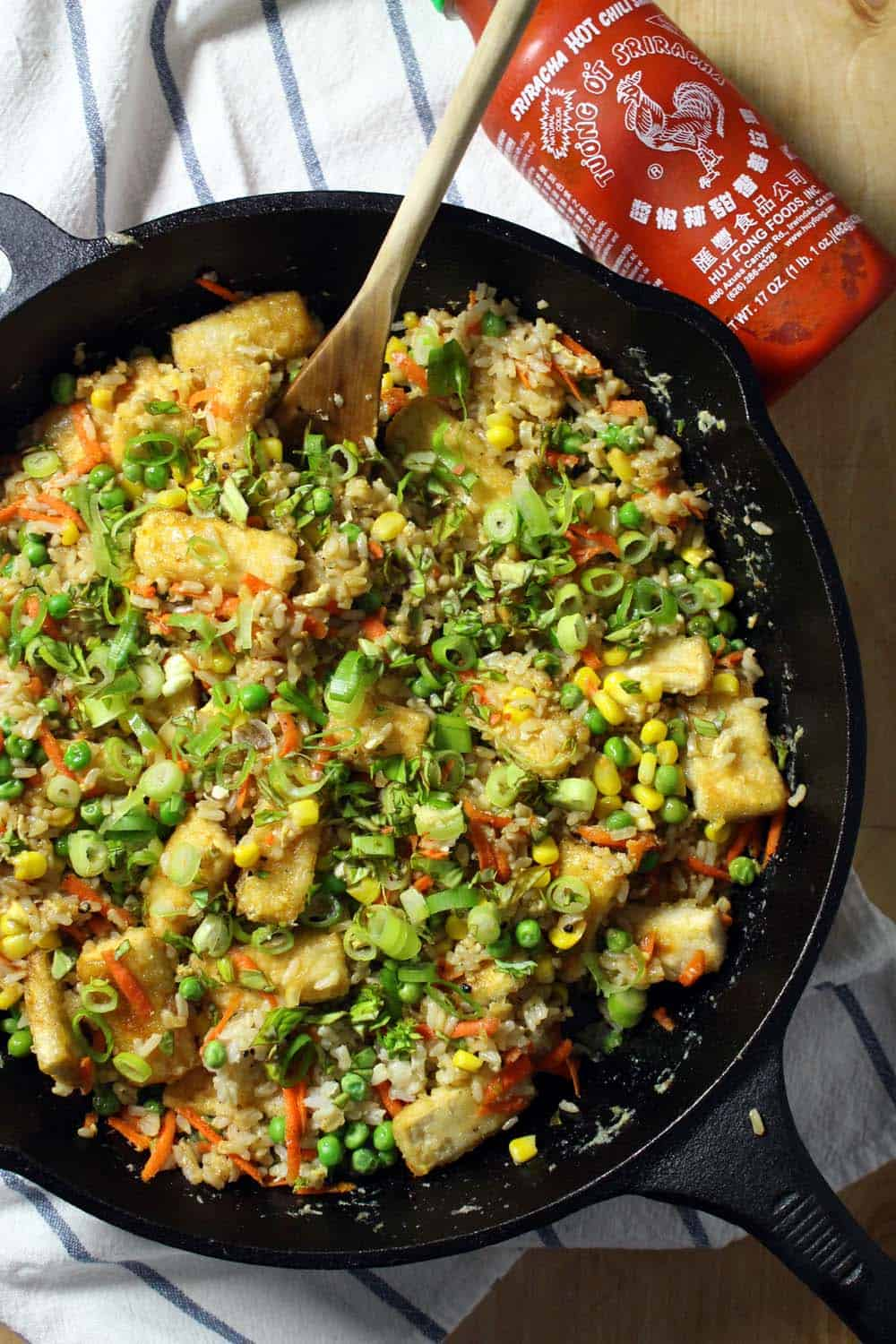 Bird's eye view of fried rice with crispy tofu in a cast iron skillet, with a wooden spoon sticking out.