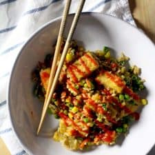 Bird's eye view of crispy tofu over fried rice in a white bowl, with chopsticks on the side and drizzled with red sauce.