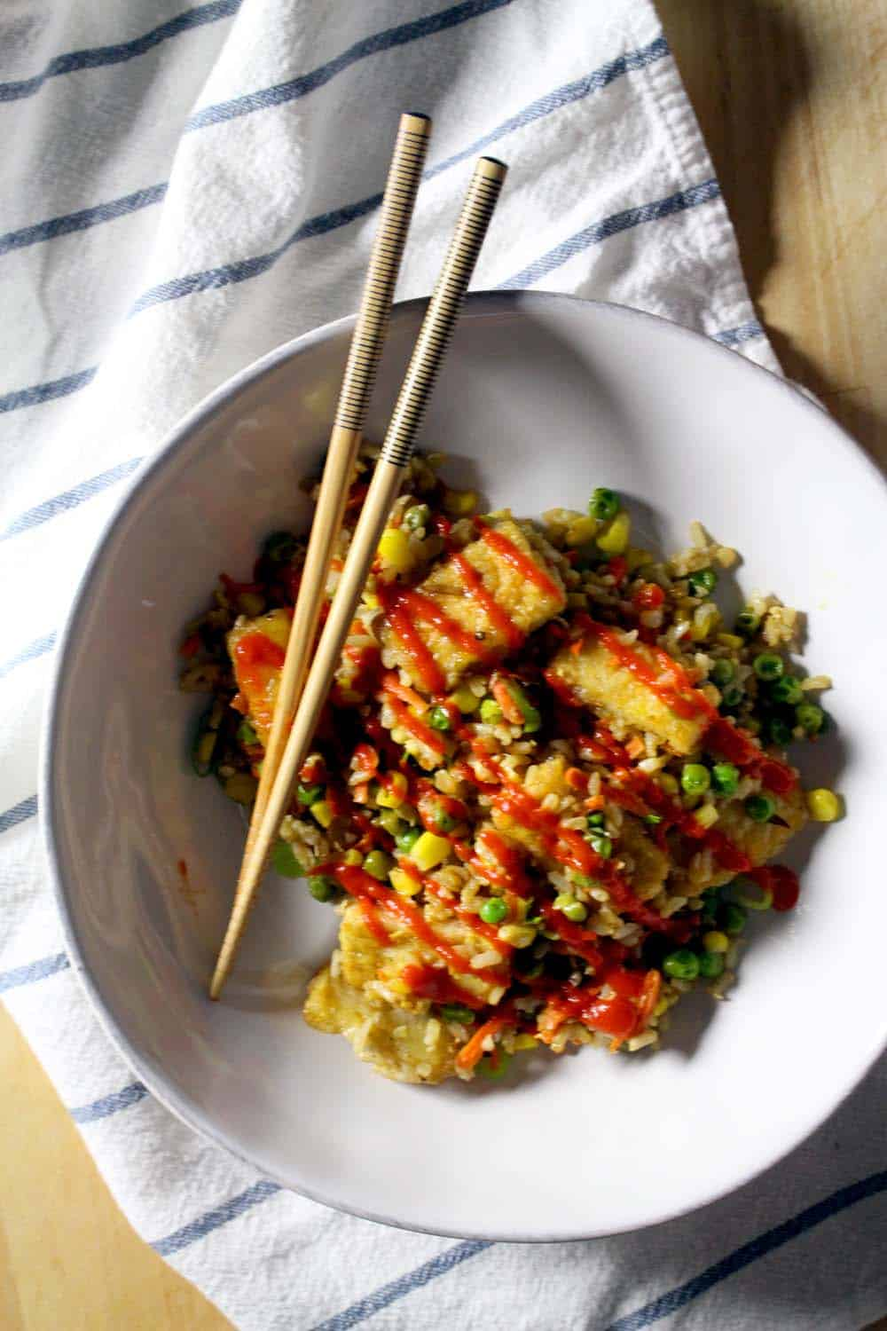 This fried rice recipe is packed with flavor, and includes how to make the tastiest, crispiest fried tofu you have ever had. Topped with scallions and basil for a super fresh taste, you'll never want take-out again!
