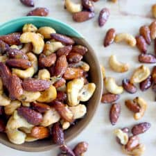 Bird's eye view of nuts in a bowl, with nuts scattered around the bowl.