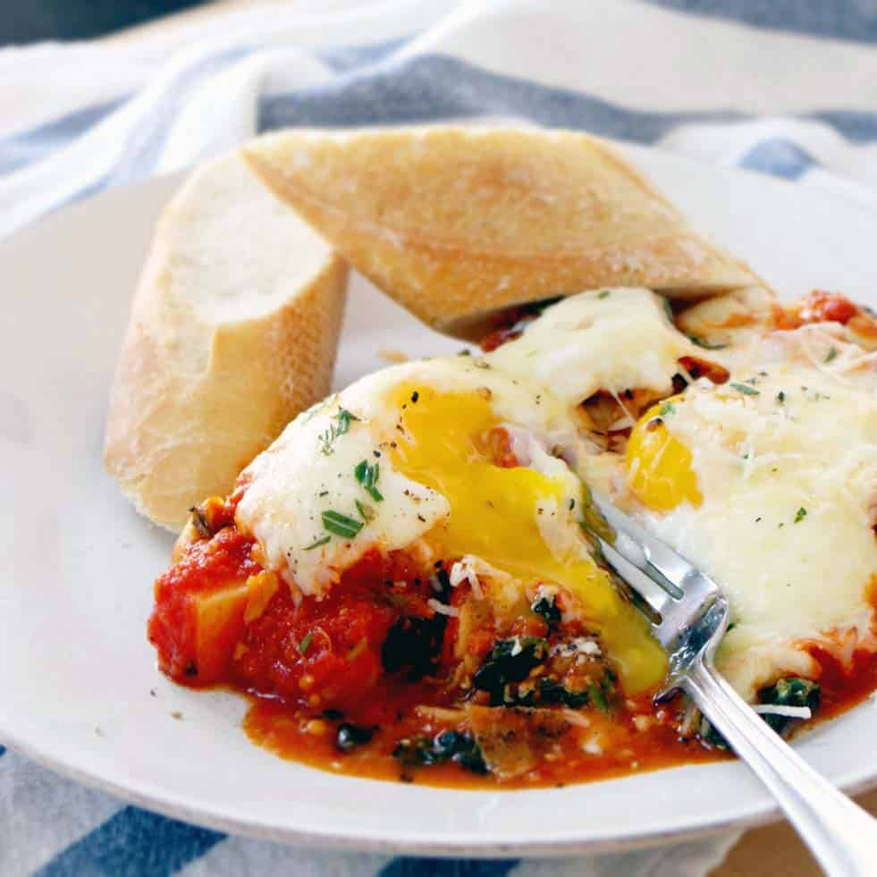 Baked Eggs with Potatoes Spinach and Marinara | Roasted rosemary potatoes are topped with spinach, marinara, eggs, and cheese and baked in the oven. This is a stress-free, delicious one pot meal that's great for a crowd or for one.