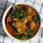 Bird's eye view of a bowl of soup with a reddish broth, spinach, orzo, and meatballs, and a spoon perched on the edge, sitting on a blue and white checkered cloth.