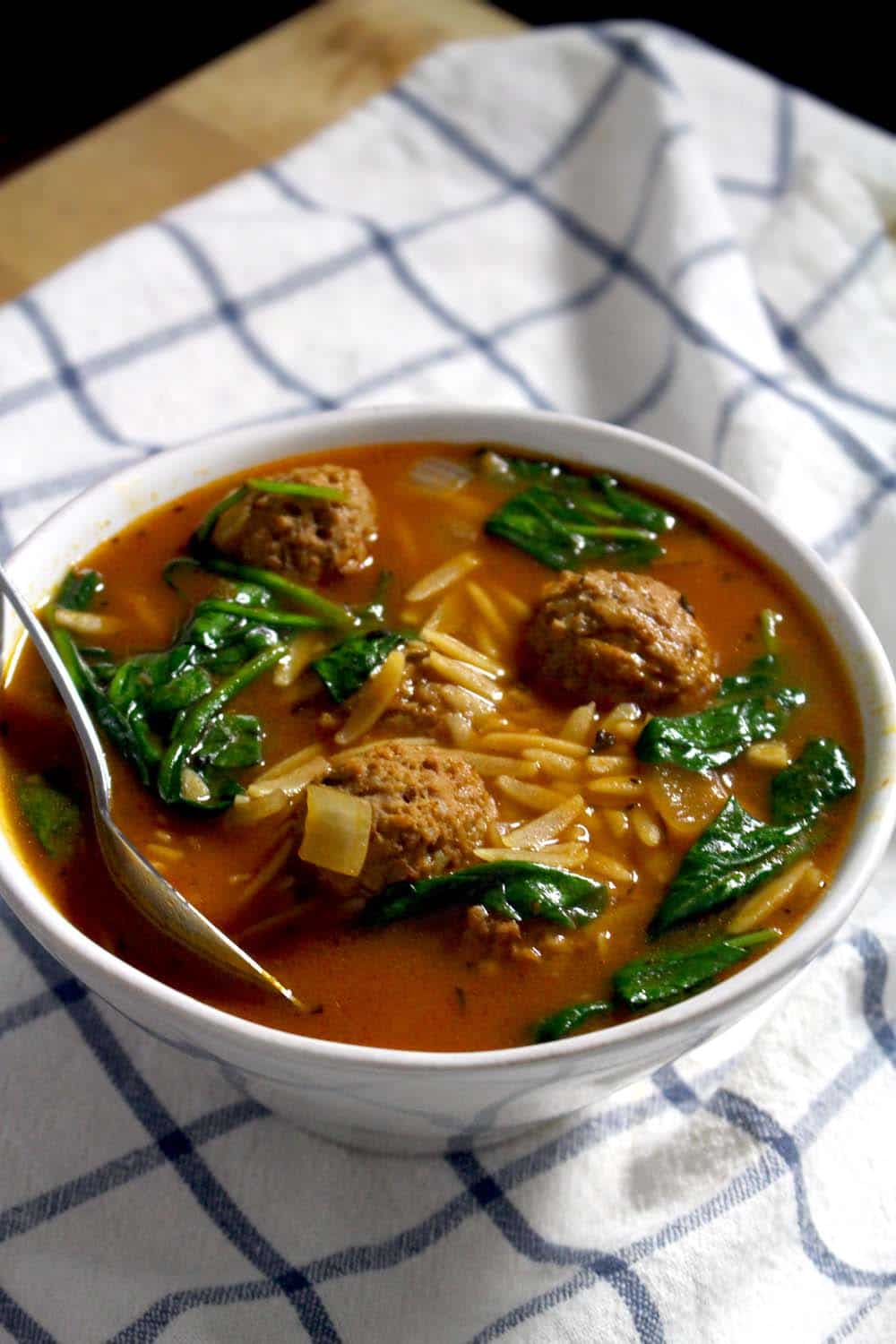 Bowl of soup with a reddish broth, orzo, spinach, and meatballs, with a spoon perched on the edge, on a blue and white checkered cloth.