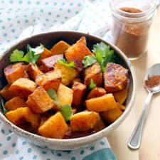 Ceramic bowl full of cubes of roasted butternut squash, with a glass jar full of spices in the background.