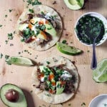 Bird's eye view of a wooden surface with open tortillas holding carnitas, sliced avocado, sour cream, hot sauce, and garnished with chopped herbs. Lime wedges, avocado, chopped herbs, and other ingredients are scattered around.