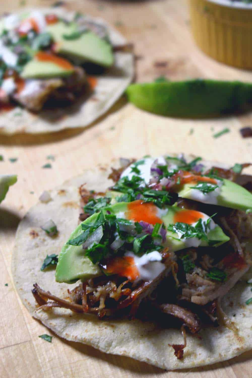 Tortillas with carnitas, sliced avocado, sour cream, hot sauce, and chopped herbs in the middle.