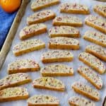 A baking sheet with biscotti on parchment paper with oranges in the background and a blue towel.