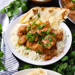 Square photo of chicken tikka masala with rice and naan.